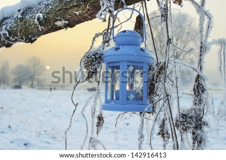 Blue lantern in winter scenery - stock photo