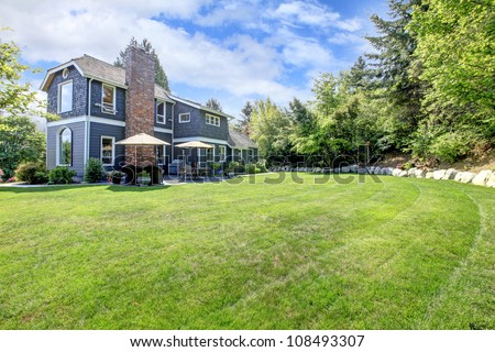 Blue large house exterior with backyard and green landscape. - stock photo