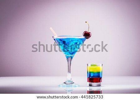 Blue light alcoholic drink with tricolor shot  - stock photo