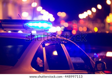 Blue light flasher atop of a police car. City lights on the background.  - stock photo
