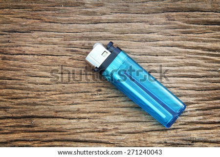 blue lighter on the wooden floor - stock photo