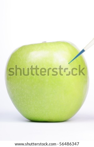 Blue liquid being injected into a Granny Smith. Studio shot. - stock photo