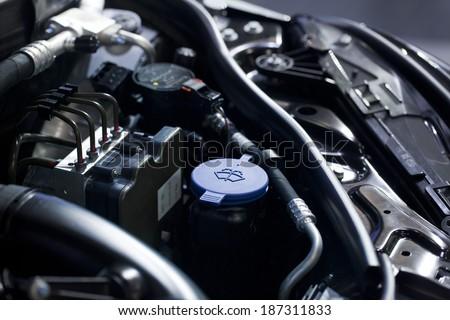Blue liquid caps inside a car engine - stock photo