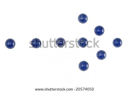 Blue marbles arranged in an arrow. - stock photo