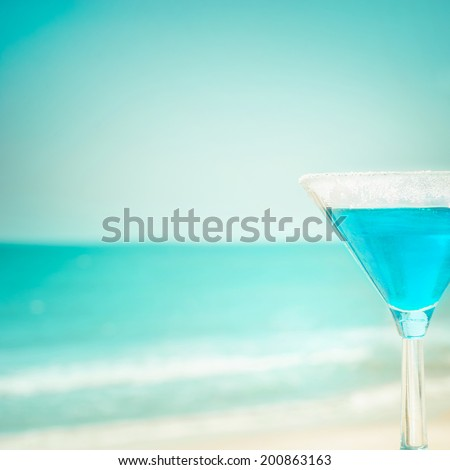 Blue margarita cocktail at tropical ocean beach. Vintage style, hipster colors image with copy space for party invitation text - stock photo