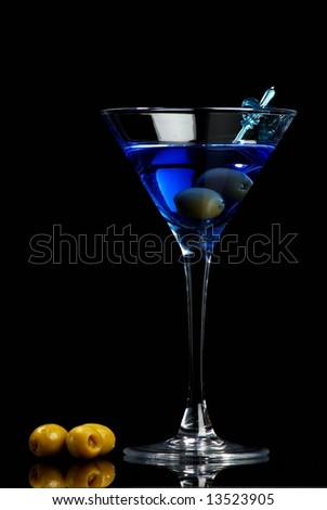 Blue martini with olives on black background - stock photo