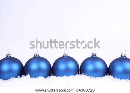 Blue matt christmas balls on snow on white background, with space for your text - stock photo