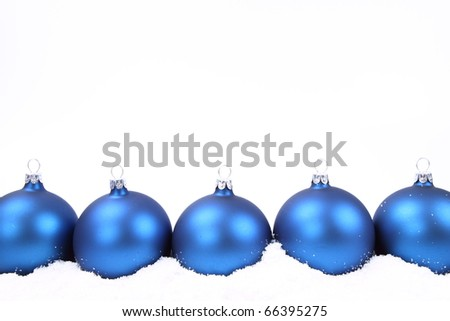 Blue matte christmas balls on snow on white background, with space for your text - stock photo