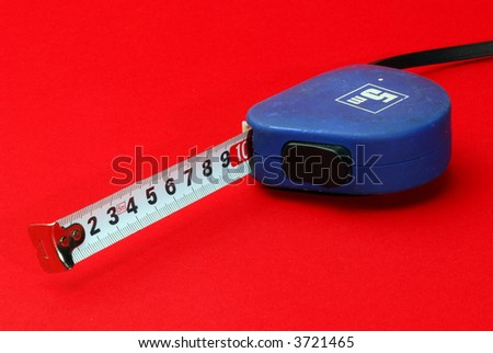 blue measurement tape on red background - stock photo