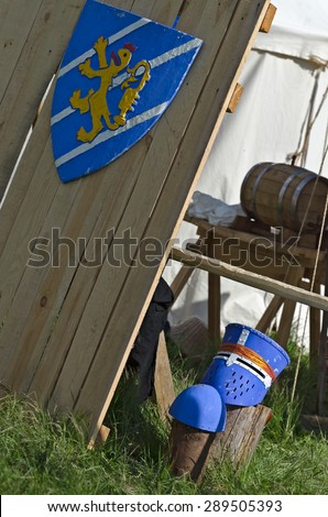 Blue medieval shield and helmet near with knights camp - stock photo