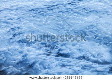 Blue melting ice surface on the frozen river water - stock photo