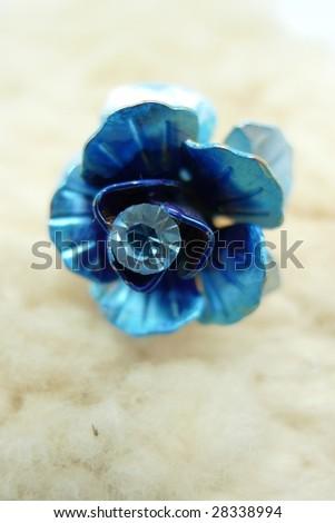 Blue metal flower on sheepskin. - stock photo