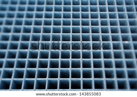 Blue metal grill floor. Tilt-shift lens used to accent the center of the steel and to emphasize the attention on it. - stock photo