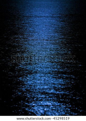 Blue moon light reflection on calm but rippled water - stock photo