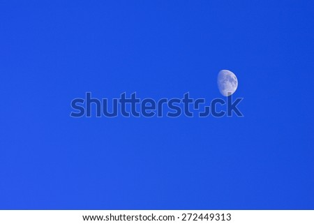 Blue moon of the Nordic bright sky. Half moon against a bright blue afternoon sky. - stock photo