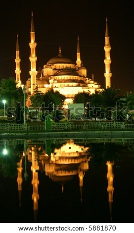 Blue Mosque by night mirroring in lake - stock photo