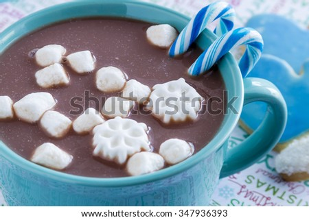 Blue mug filled with hot chocolate with snowflake marshmallows, blue candy canes and frosted mitten cookies - stock photo