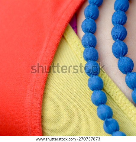 Blue necklace with yellow top and red cardigan - stock photo