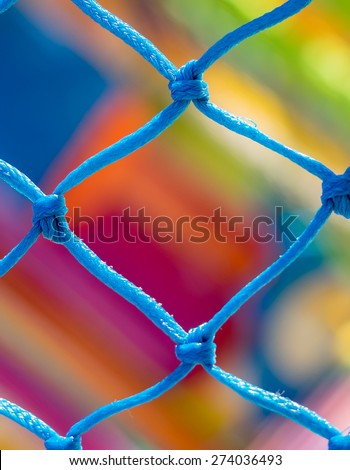 Blue net close up and very colorful background in children playground - stock photo