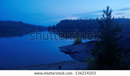 blue night over calm remote lake - stock photo