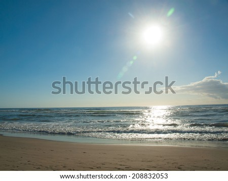 Blue Ocean Waves Breaking on the Beach as the Sun is Going Down - stock photo
