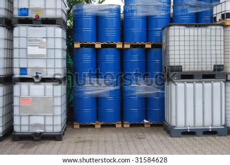 Blue oil drums and plastic container - stock photo