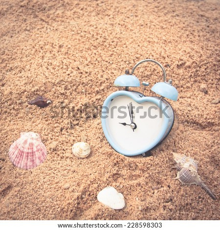 blue old retro clock on sand beach and sea shell vintage color tone,abstract background to memory of last time.  - stock photo