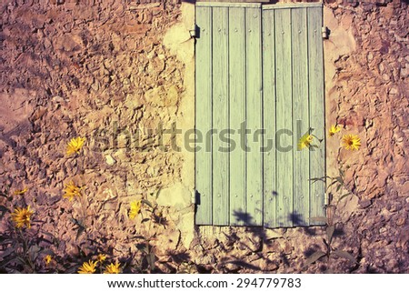 Blue old wooden window in a stone house wall  - stock photo