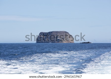 Blue Pacific Ocean and Inhabited island with clear blue sky. Galapagos Islands. Ecuador 2015 - stock photo