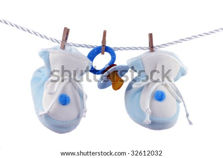 Blue pacifier and booties hanging on a cord, isolated on white - stock photo