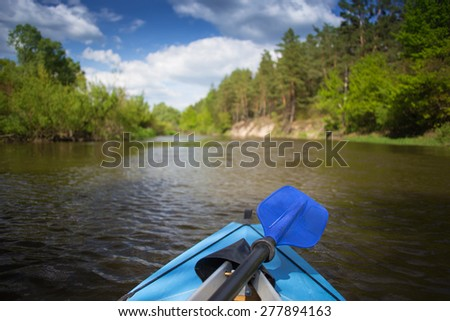 Blue paddle lying on kayak. Kayaking on a river - stock photo