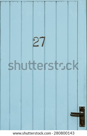 Blue painted weathered door number 27 twenty seven closeup - stock photo