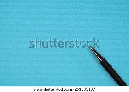 Blue paper background with black ball pen and text space - stock photo