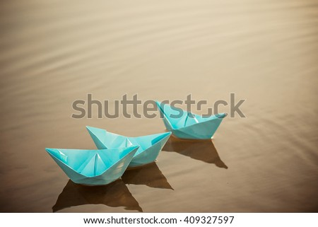 Blue paper boat on the water - stock photo