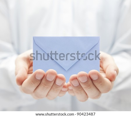 Blue paper envelope in hands - stock photo
