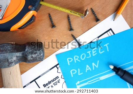 Blue paper with home improvement project plan, tools kit on a wood background - stock photo