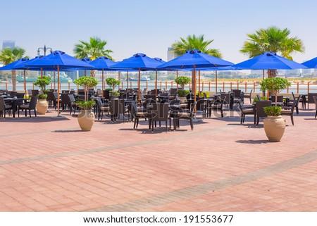 Blue parasols at the sea in Abu Dhabi, UAE - stock photo