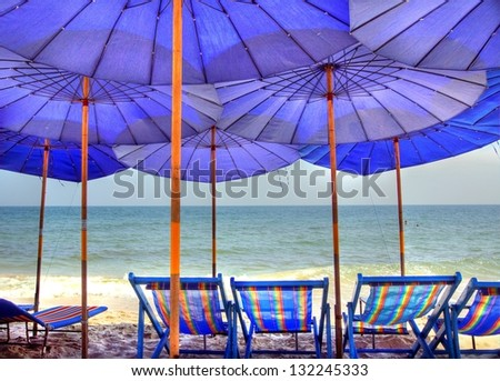 Blue parasols on the beach provide shade in the sunshine - stock photo