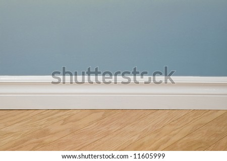 Blue pastel wall, baseboard and hardwood flooring - stock photo