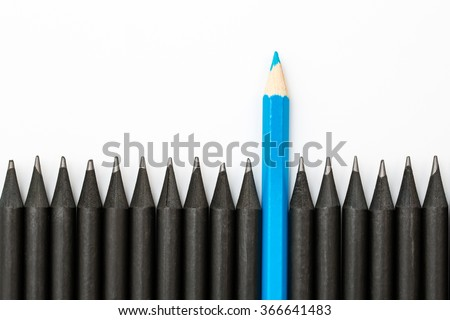 Blue pencil standing out from the row of black pencils. - stock photo