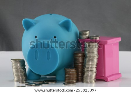 blue piggy bank and Stacks of money coins and pink safe gray background. - stock photo