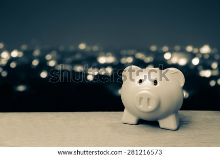 blue piggy bank on blur light in city background in vintage tone - stock photo