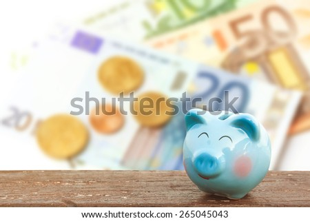 blue piggy bank on wooden table over blurred  banknote background,money and saving concept. - stock photo