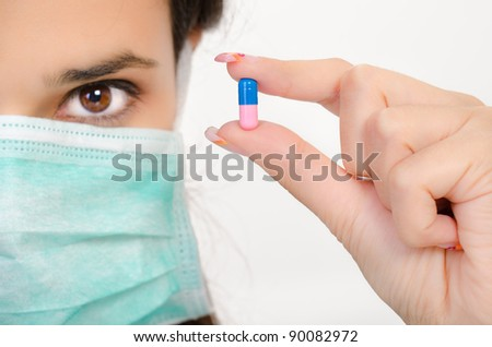 Blue pink pill in a woman's hand, isolated an a white background - stock photo
