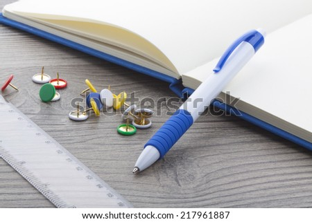Blue plastic ball pen with office supplies on wooden table. - stock photo