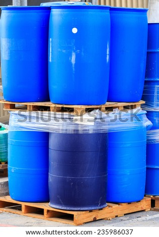 Blue plastic barrels on paletts in a chemical plant - stock photo