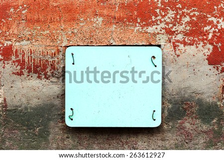 Blue plastic plate closes the window on an old gloomy wall with cracks, scratches and paint residues - stock photo