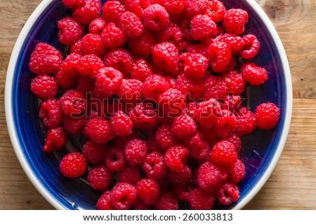 Blue plate full of juicy,delicious, healthy raspberries. - stock photo