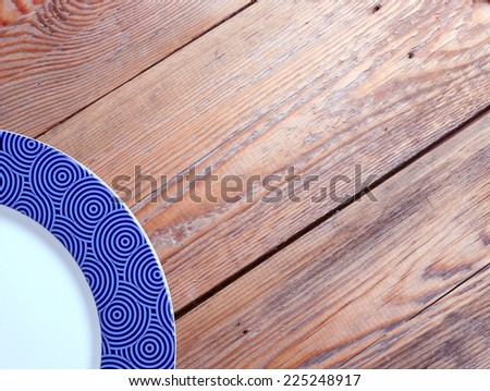 Blue plate lying on a wooden table - stock photo