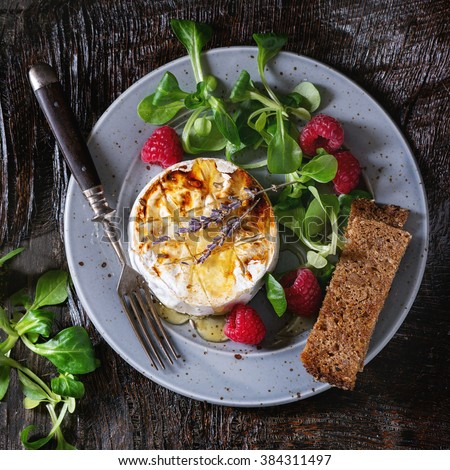Blue plate with grilled goat cheese served with liquid honey, lavender, raspberries, wholegrain toast and green salad. With vintage fork over wooden table. Dark rustic style. Flat lay. Square image - stock photo